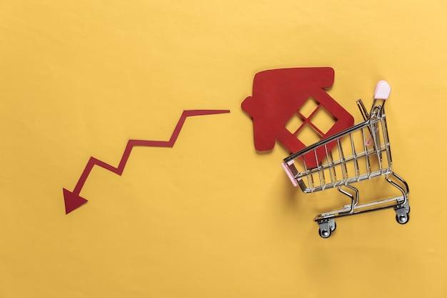 Recessie van verkopen en aankopen van woningen winkelwagentje met een huis, drop pijl op een gele