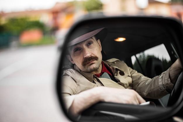 Rechercheur in zijn auto weerspiegeld in een spiegel tijdens het stalken