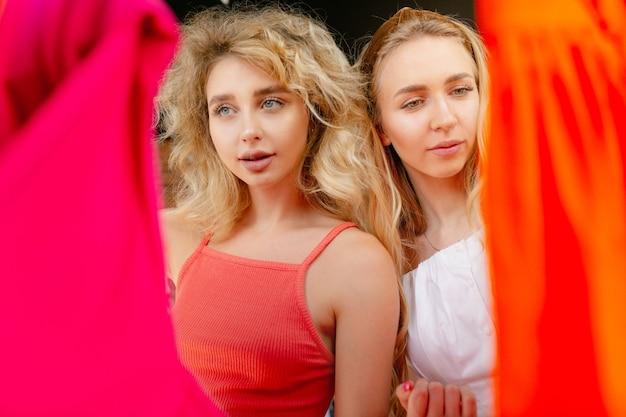 Recht kiezen. slijtage, kledingwinkel tijdens uitverkoop, zomer- of herfstcollectie. jonge vrouwen op zoek naar nieuwe kleding. concept van mode, stijl, aanbiedingen, emoties, verkoop, aankopen. gloednieuw winkelen.