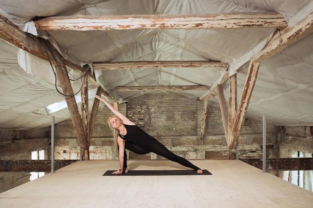 Rechtdoor. een jonge atletische vrouw oefent yoga op een verlaten bouwgebouw. geestelijke en lichamelijke gezondheid. concept van een gezonde levensstijl, sport, activiteit, gewichtsverlies, concentratie.