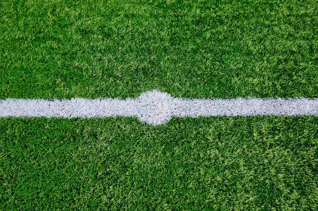 Rechte witte krijtlijn die op grasachtergrond merken.
