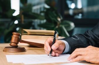 Rechter die pen houden die document over houten bureau controleren