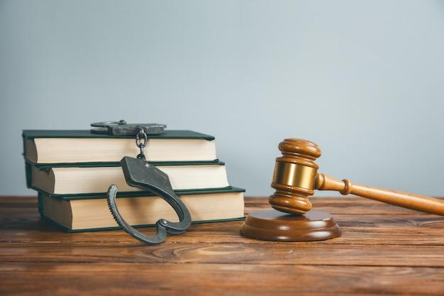 Rechter en handboeien op boek op tafel