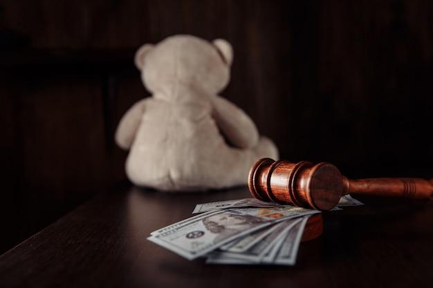 Rechter hamer dollar bankbiljetten en teddybeer als een symbool kinderrechten