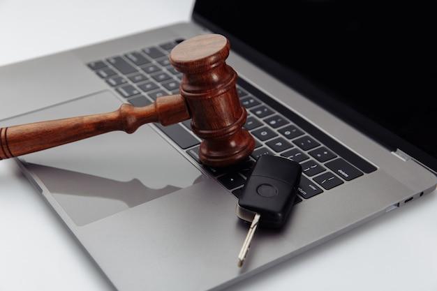 Rechter hamer en autosleutels op laptop computertoetsenbord. symbool van recht, gerechtigheid en online autoveiling.