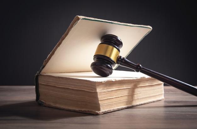 Rechter hamer en boek op de houten tafel.