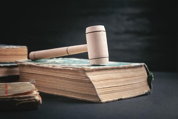 Rechter hamer en boek op de zwarte achtergrond.