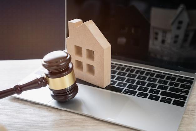 Rechter hamer en huis model op notebook computer, online veiling voor onroerend goed concept