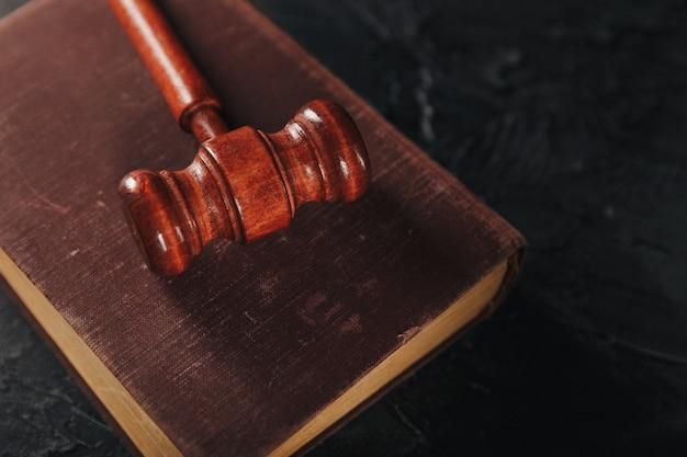 Rechter hamer en juridisch boek over houten tafel.