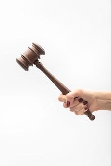 Rechter hamer in vrouwelijke hand op witte achtergrond. vrouw rechter concept. verticaal frame.