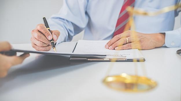 Rechter hamer met advocaten van justitie met teamvergadering op advocatenkantoor concepten van recht en juridische dienstverlening.