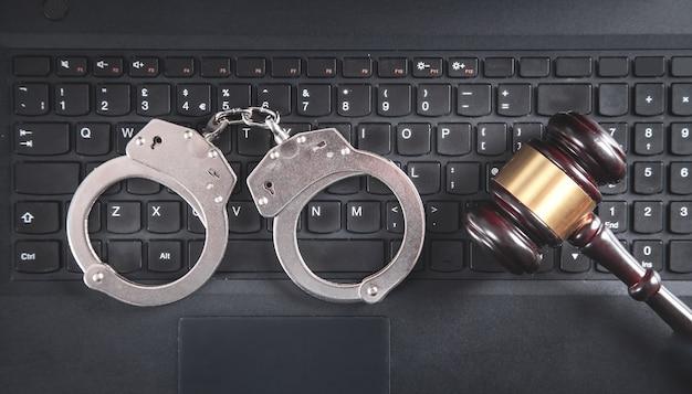 Rechter hamer met handboeien op laptop toetsenbord.