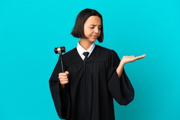 Rechter over geïsoleerde blauwe achtergrond die copyspace met twijfels vasthoudt