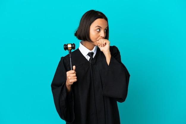 Rechter over geïsoleerde blauwe achtergrond die de mond bedekt en naar de zijkant kijkt