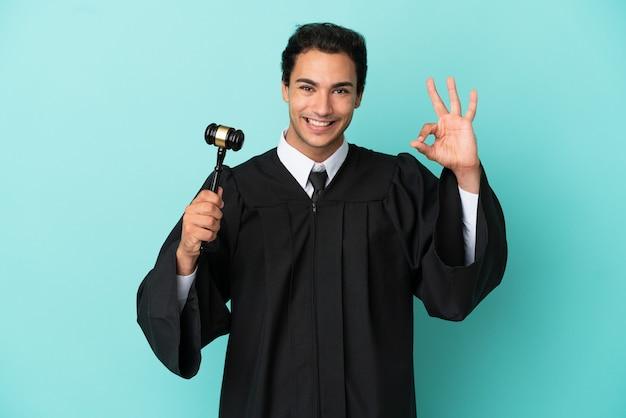 Rechter over geïsoleerde blauwe achtergrond die ok teken met vingers toont