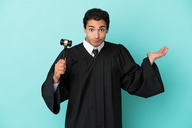 Rechter over geïsoleerde blauwe achtergrond die twijfels heeft terwijl hij zijn handen opsteekt