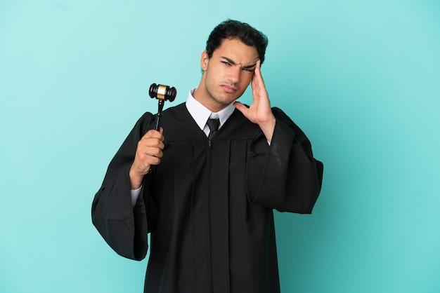 Rechter over geïsoleerde blauwe achtergrond met hoofdpijn