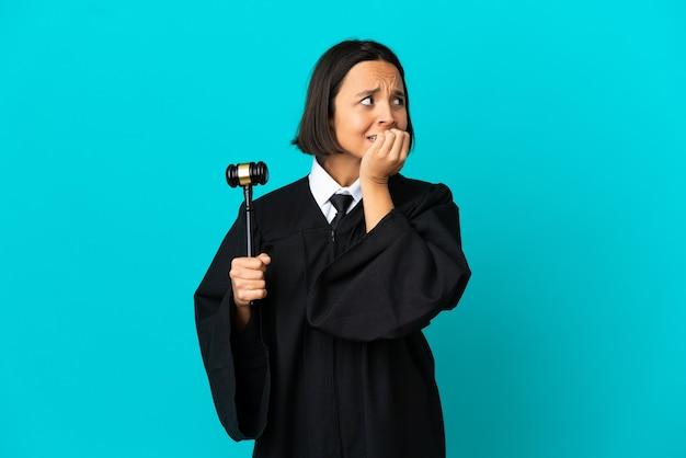 Rechter over geïsoleerde blauwe achtergrond nerveus en bang om de handen in de mond te leggen