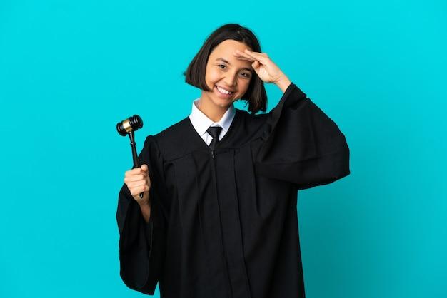 Rechter over geïsoleerde blauwe achtergrond saluerend met de hand met gelukkige uitdrukking