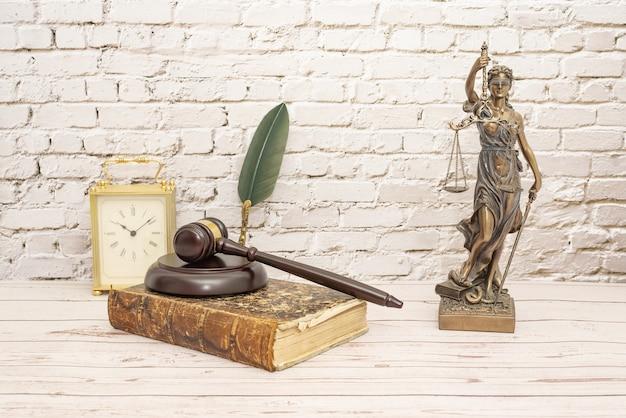 Rechter's hamer en symbool van rechtvaardigheid whit boek en klok.