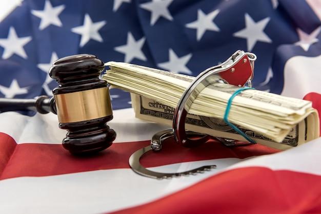Rechter's voorzittershamer met handboeien en dollarbiljetten boven vlag od amerika. wet of misdaad concept. justitie