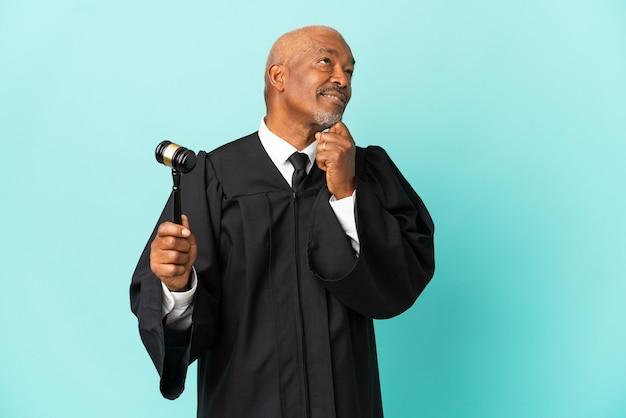 Rechter senior man geïsoleerd op blauwe achtergrond en opzoeken