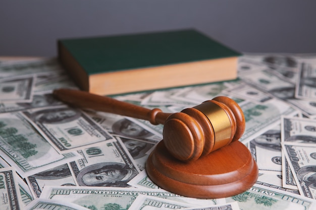 Rechter voorzittershamer met dollars en wetboeken