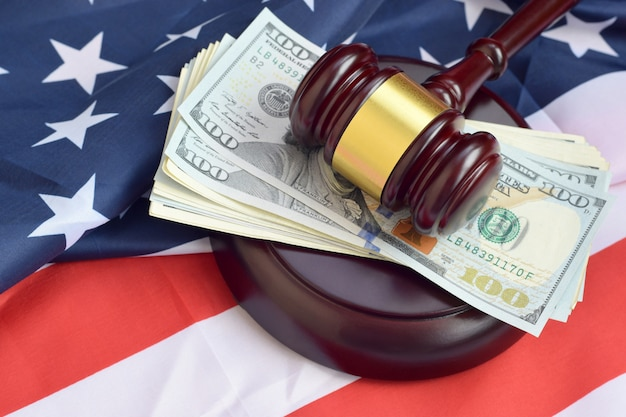 Rechterhamer en geld op de vlag van de verenigde staten van amerika. vele honderd dollarsrekeningen onder rechter boosheid op de vlag van de vs oordeel en omkoping