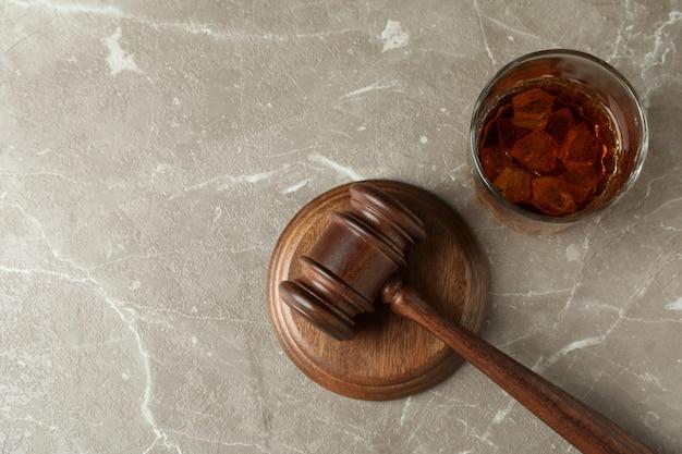 Rechterhamer en glas whisky op grijze getextureerde tafel