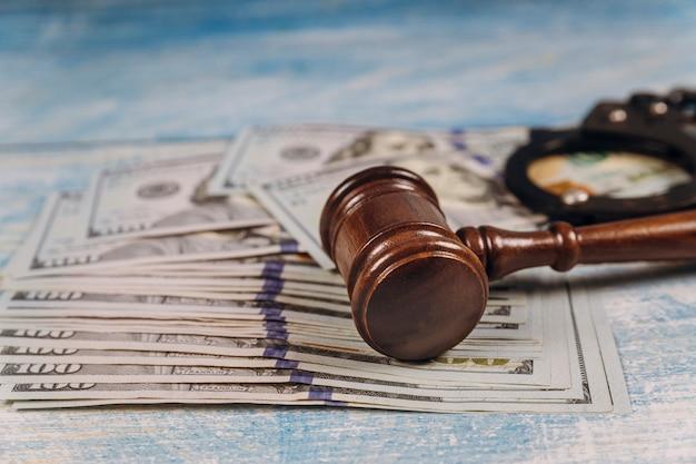 Rechterhamer van metalen politiehandboeien en amerikaanse dollar corruptie, vuile geld financiële misdaad