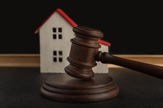 Rechters hamer op achtergrond van modelhuis. schik een rechtszaak over huisdeal. in beslag genomen woningen. concept van het oplossen van eigendomsgeschillen.