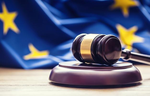 Rechters houten hamer met eu-vlag op de achtergrond. symbool voor jurisdictie.