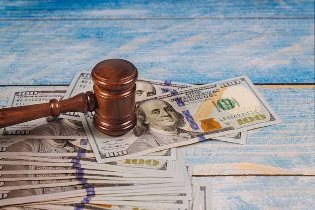 Rechtershamer en geld op blauwe houten lijst.