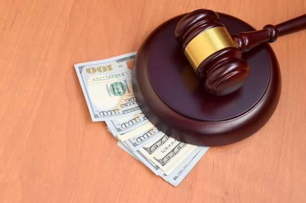 Rechtershamer en geld op bruine houten lijst