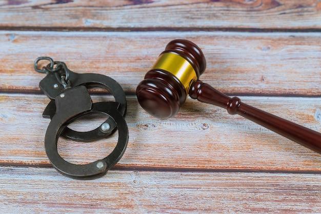 Rechtershamer en handcuffs op houten achtergrond.