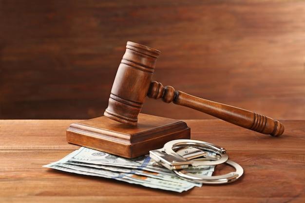 Rechtershamer, handboeien en geld op houten achtergrond