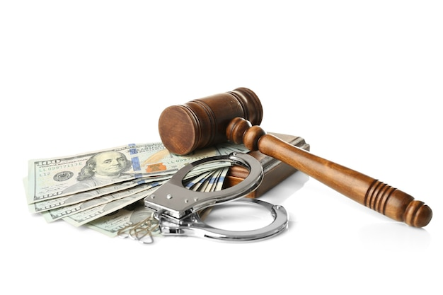 Rechtershamer, handboeien en geld op witte achtergrond