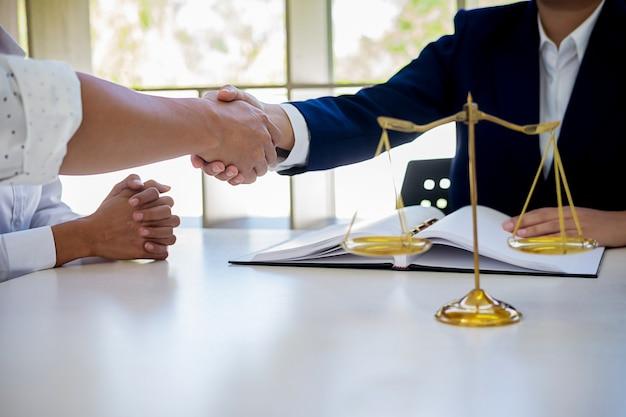 Rechtershamer met rechtvaardigheidsadvocaten die teamvergadering hebben bij wetsfirma op achtergrond