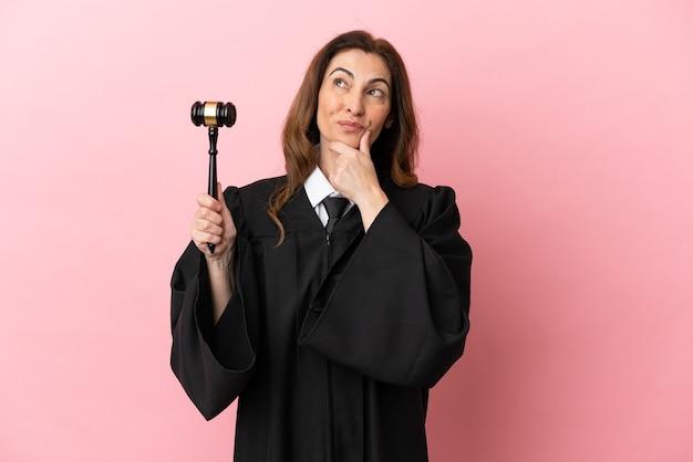 Rechtervrouw van middelbare leeftijd die op roze achtergrond wordt geïsoleerd die twijfels heeft