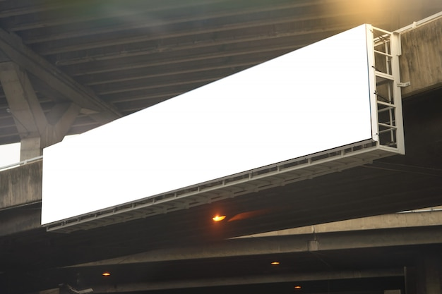 Rechthoekig bilboard hangt aan de zijstang van het viaduct of de hoge weg met de zon flare met kopie tekst ruimte