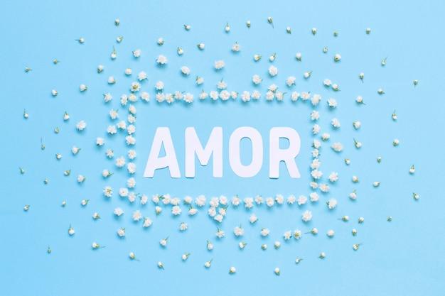 Rechthoekig bloemenkader en tekst amor op een lichtblauwe bovenaanzicht als achtergrond