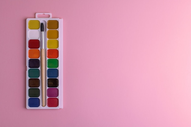 Rechthoekig doospalet met honingkleurige aquarellen en een penseel op een roze achtergrond.