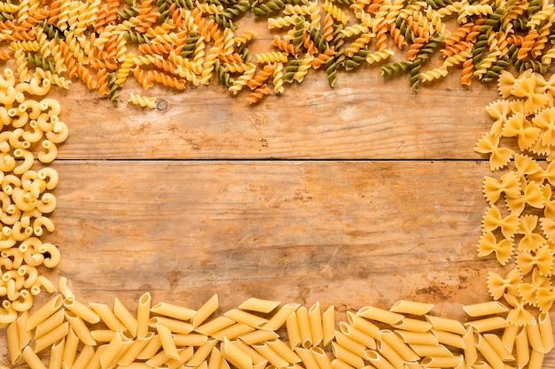 Rechthoekig frame gemaakt met verschillende soorten rauwe pasta op houten tafel