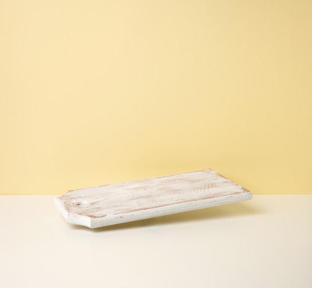 Rechthoekig leeg wit houten keukenbord op gele achtergrond, gebruiksvoorwerpen