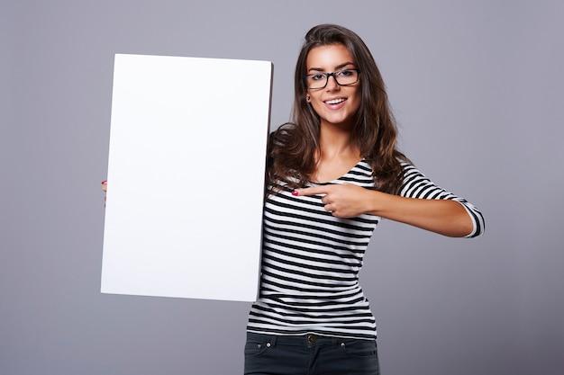 Rechthoekig wit bordje in handen van aantrekkelijke brunette