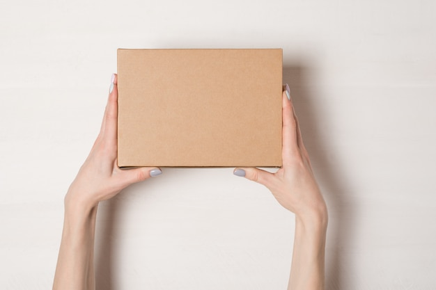 Rechthoekige doos in vrouwelijke handen. bovenaanzicht witte tafel