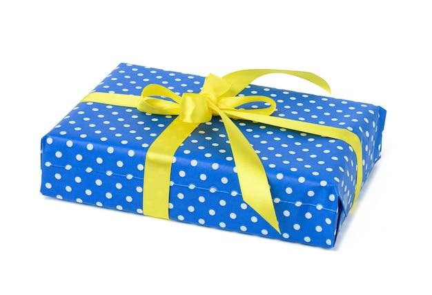 Rechthoekige doos verpakt in blauw papier met witte stippen en vastgebonden met geel zijden lint op een witte achtergrond