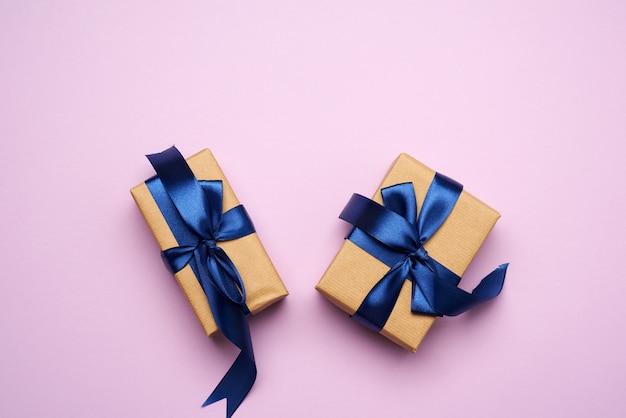 Rechthoekige doos verpakt in bruin papier en gebonden met een blauw zijden lint met een strik, cadeau op een paarse achtergrond, bovenaanzicht, kopie ruimte