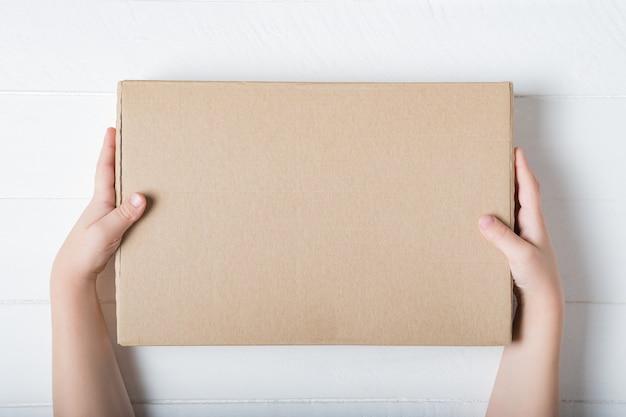 Rechthoekige kartonnen doos in kinderhanden. bovenaanzicht,