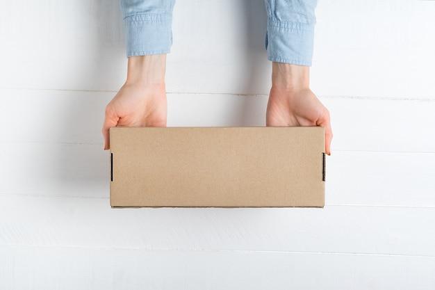 Rechthoekige kartonnen doos in vrouwelijke handen. bovenaanzicht, wit oppervlak